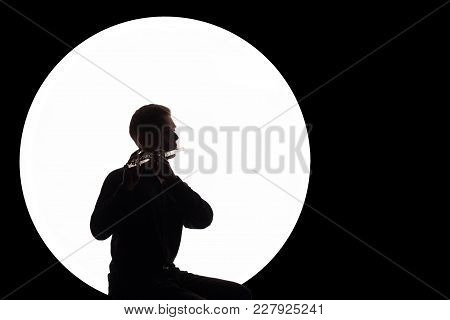 Concept Music For The Full Moon. Night Background. Silhouette Of A Guy In A White Circle Who Plays T