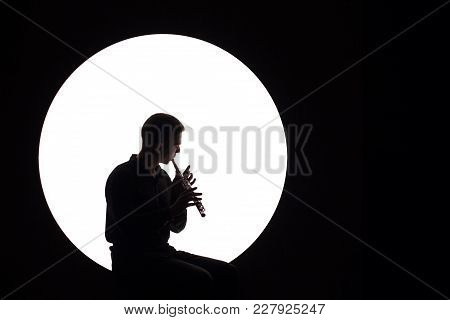 Concept For Music News. Silhouette Of A Musician Who Plays The Flute. White Circle As The Moon On A