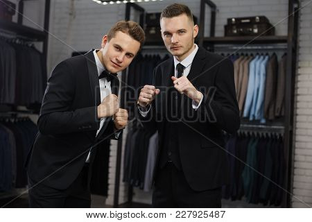 Two Handsome Young Mans In Classic Vest Against Row Of Suits In Shop