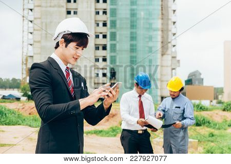 Asian Engineer Holding Smartphone Work Concept Teamwork Of Building Construction. Project Contractor