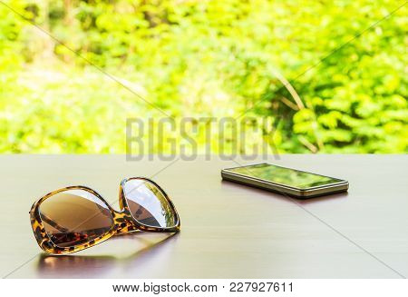 Brown Fashion Sun Glasses And Black Smartphone On Wooden Brown Table Outside Room Inside Big Forest