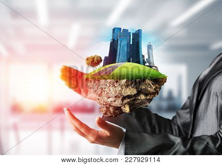 Closeup Of Business Woman In Suit Keeping Green Island With Skycraper City In Her Hands With Sunligh