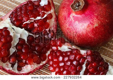 Pomegranate Fruit Cut In Half. Bright Juicy Ripe Pomegranate Seeds.