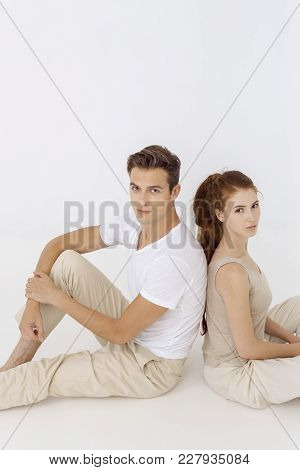 Confident Young Couple Sitting With Back To Each Other On Floor, Serious. Young Caucasian Woman And