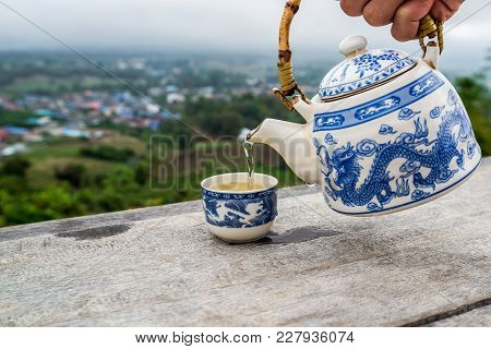 Pouring Tea Into A Cup That Was Placed On Wooden Table Porch With Village Mountain View Behind, Trav
