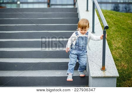 A Small Child Learns To Go Down The Stairs