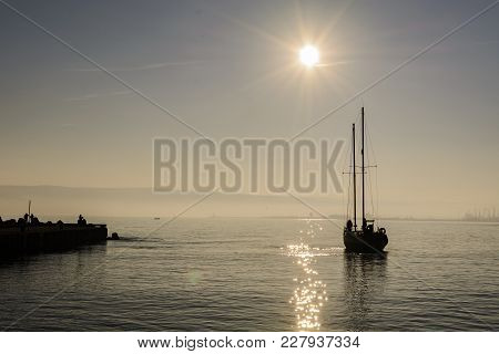 Silhouette Of A Sailboat With Crew On Board