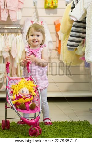 Little Cute Blue-eyed Blonde Girl Smiling And Clapping Her Hands In The Kids' Store With The Toy Bab