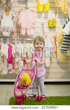 Little Blonde Girl Smiling And Clapping Her Hands In The Kids' Store With The Toy Baby Carriage