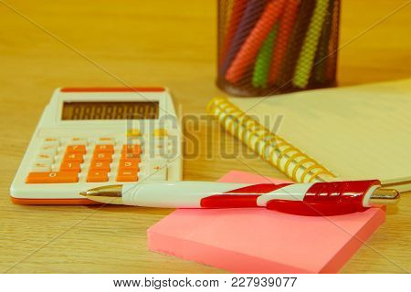 Sales Report Analysis With Pen And Calculator. Graphics Calculator And Pen