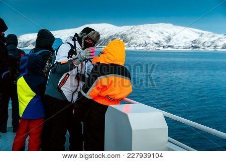 Man Adjusts The Hood Of Warm Winter Coat On A Woman, Standing On The Deck Of The Ship. Snow-covered