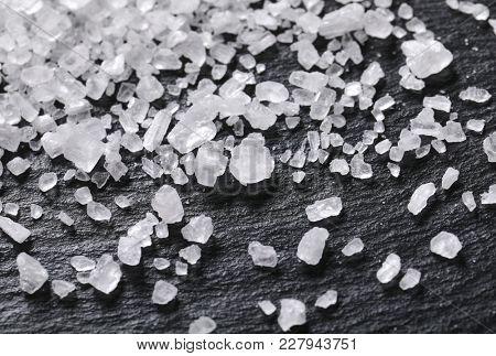 crystals of coarse grained sea salt on black background - detail