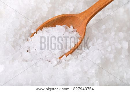 coarse grained sea salt on a wooden spoon - close up