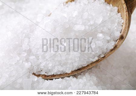 coarse grained sea salt on a wooden spoon - detail