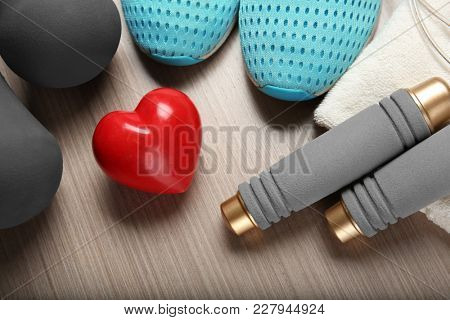 Gym stuff and red heart on wooden background. Cardio training concept