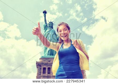 Statue of Liberty New York City tourist woman happy doing thumbs up. Asian girl on summer vacation travel on Liberty Island, USA. Young chinese exchange student woman with bag .
