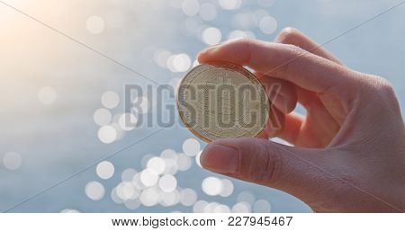 Holding bitcoin over seascape background