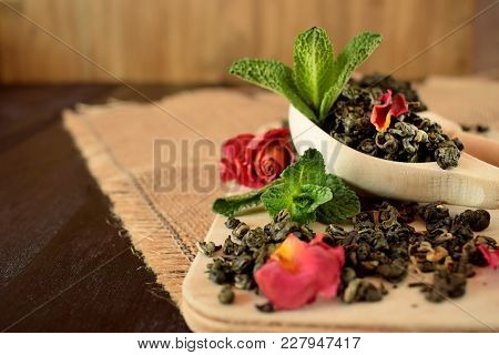 Leaf Tea, Dried Rose And Fresh Mint For Making Tea On A Wooden Board