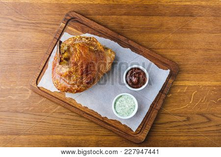 Top View Of Gourmet Roasted Pork Knuckle With Sauces On Wooden Tabletop