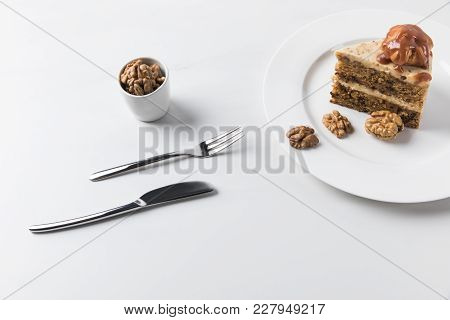Cutlery And Plate With Cake Placed On White Surface