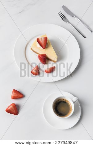 Coffee Cup With Cheesecake And Sliced Strawberries On Plate