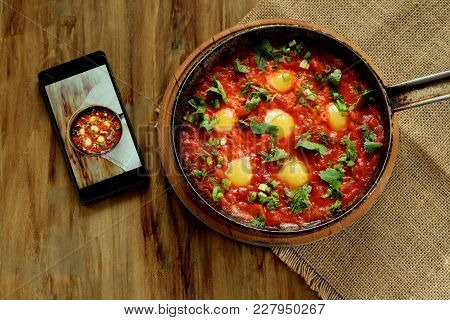 Fried Eggs In Tomato Sauce In A Cast Iron Pan And A Smartphone With The Photo On A Wooden Table