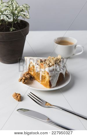 Coffee Cup, Cake And Cutlery With Potted Plant On Table