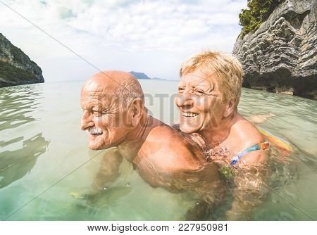 Senior Couple Vacationer Having Genuine Playful Fun On Tropical Beach In Thailand - Snorkel Tour In