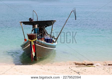 Local Fisherman With Wooden Long Tail Boat On The Beach In Thailand