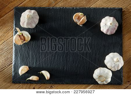 Garlic Composition On Black Flat Piece Of Board On Rustic Rough Wooden Background Copy Space For You