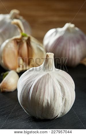 Garlic On Flat Wooden Plate Put On Rustic Rough Wooden Table With Light Grey Cotton Canvas As Backgr