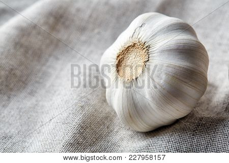 Close Up View Of Ripe Garlic Bulb Arranged On A Light Grey Cotton Napkin Or Tablecloth, Shallow Dept