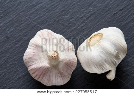 Close Up View Of Two Ripe Garlic Bulbs Arranged On A Black Piece Of Board, Shallow Depth Of Field, S