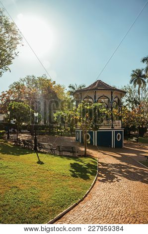 Old And Colorful Gazebo Of Square In The Middle Of Verdant Garden Full Of Trees, In A Bright Sunny D