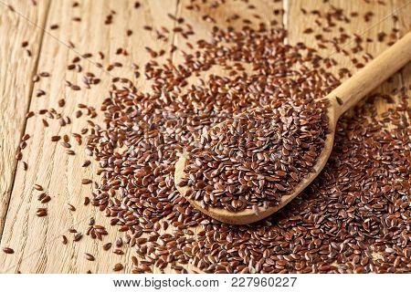 Top View, Close-up Picture Of Wooden Spoon Full Of Flax Seeds Over Some Seeds Composed On Rustic Bro