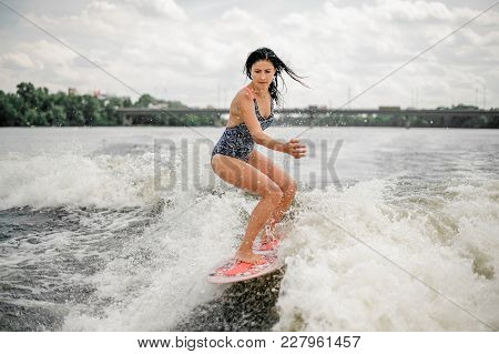 Young Pretty Slim Brunette Woman Riding Wakeboard On Wave Of Motorboat Having Nice Summertime At The