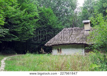 One Rural Old House, Covered With Straw Near A Dirt Path In Front Of A Coniferous Forest On A Clear