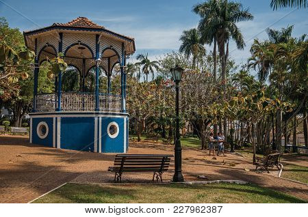 Sao Manuel, Southeast Brazil - September 09, 2017. Old Colorful Gazebo And People Amid Garden Full O