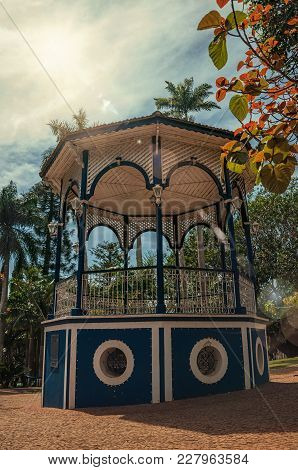 Close-up Of Old Colorful Gazebo Amid Verdant Garden Full Of Trees And Sunshine At Sao Manuel. A Cute