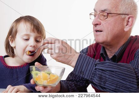 Grandpa Feeding His Grandchild With Fruits Salad. (healthy Foods, Vitamins, Generation, Relationship