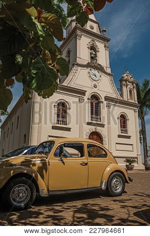 Sao Manuel, Southeast Brazil - September 09, 2017. Church Facade With Parked Car And Evergreen Garde