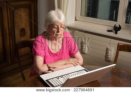 Elderly Woman Sitting On Her Laptop And Writing A Letter