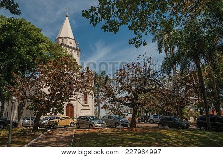 Sao Manuel, Southeast Brazil - September 09, 2017. Church Facade With Parked Cars And Evergreen Gard