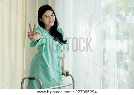 Young Asian Patient Woman Standing With Folding Walker At Hospital Room Showing Victory Sign For Che