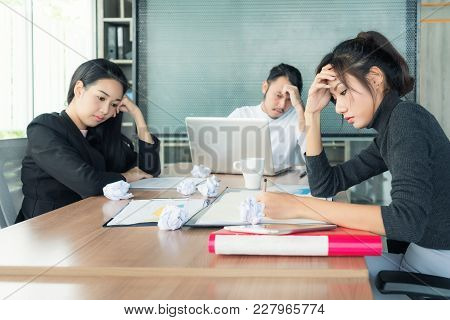 Group Of Unhappy Asian Business People In Casual Suit Sitting In Business Meeting Room And Looking S