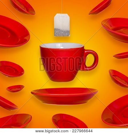 Creative Surreal Design With A Red Coffee Cup And Saucer And Tea Bag On A Yellow Background. A Cup A