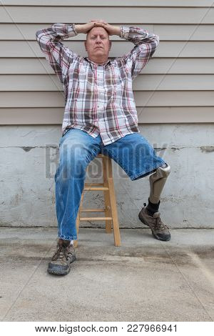 Amputee Man Sitting On A Stool, Prosthetic Leg Out, Hands On Head Looking At Camera, Copy Space, Ver