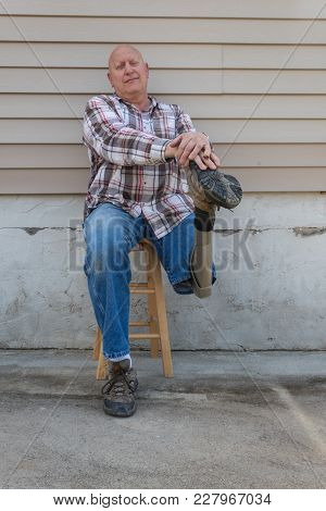 Seated Amputee Man Resting Hands On Shoe Of Prosthetic Leg, Copy Space, Vertical Aspect