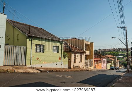 Sao Manuel, Southeast Brazil - October 14, 2017. Downhill Street View With Sidewalk Walls And Colorf