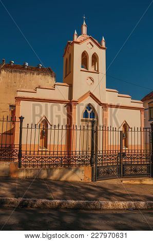 Facade Of Small Church And Belfry Behind Iron Fence, In A Sunny Day At Sao Manuel. A Cute Little Tow